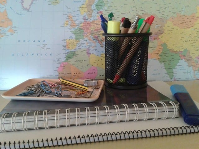 Cup with pens and pencils on top of a notebook