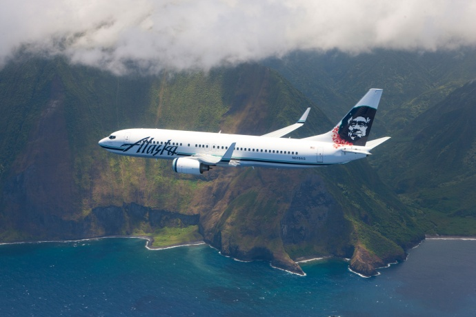 An Alaska Airlines Jet flying above the Molokai Cliffs