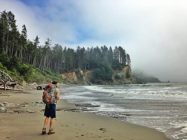 travel deals, man backpacking on the beach Brads Deals
