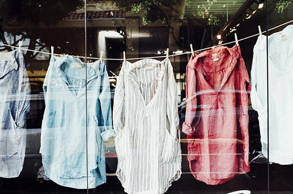 five shirts in a window on a laundry line