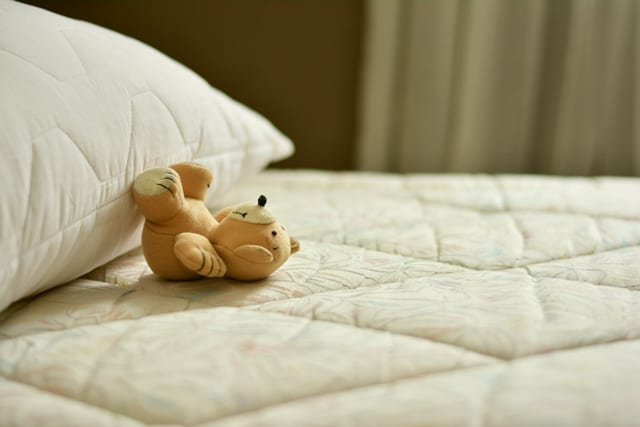 a teddy bear and pillow on a mattress