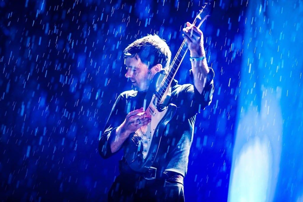 Man playing guitar in the rain