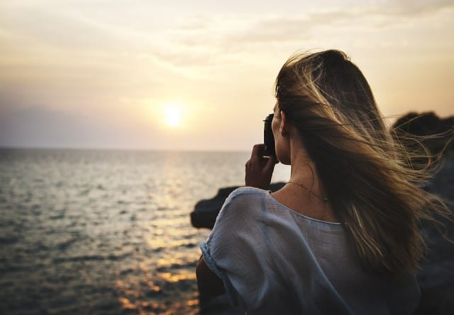 women taking a photo of a sunset