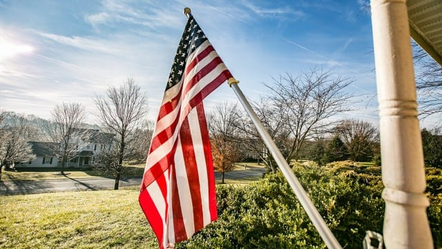 an American flag hanging on a front porch