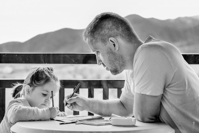 girl practicing writing with her dad