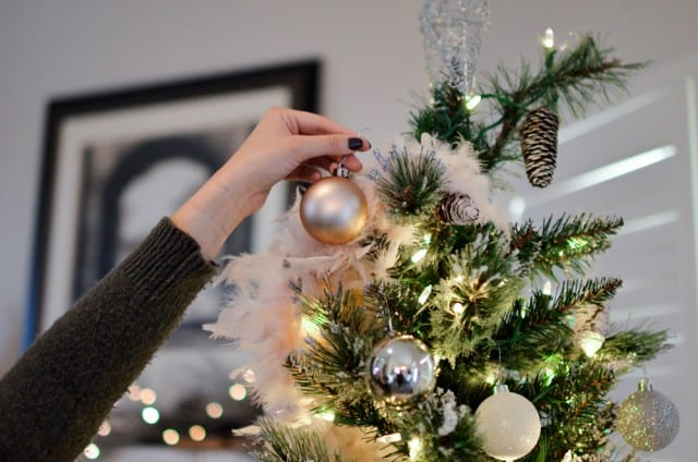 a woman's hand placing a ornament on a christmas