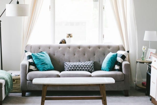 a grey sofa with blue pillows and coffee table
