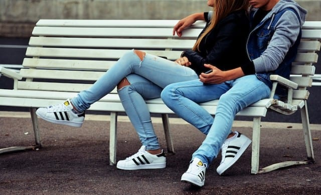 a couple sitting on a bench with adidas shoes