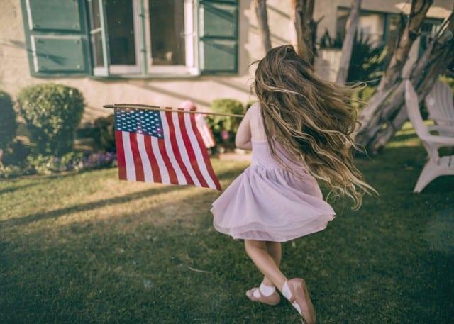 little girl carrying American flag