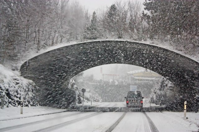 car going under a snowy bridge