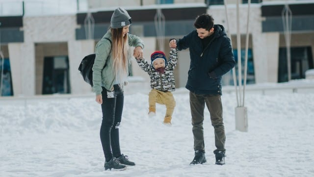 couple playing with child in the snow