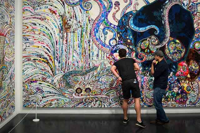 two men admiring an art collection