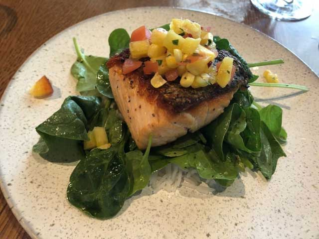 a piece of salmon on a bed of spinach