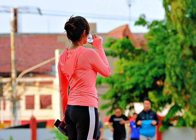 woman in leggings drinking water